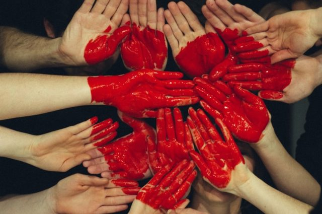 a group of hands forming together with a large painted heart